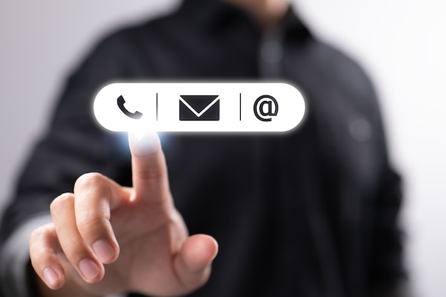Ein geschäftsmann wird gesehen, wie er die symbole für e-mail-telefon und adresse drückt. kontaktieren sie uns konzept