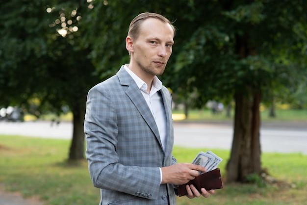 Ein geschäftsmann zählt geld in seiner brieftasche.