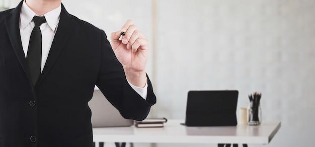 Ein geschäftsmann zeigt mit dem stift zum schreiben an bord, während er im besprechungsraum steht
