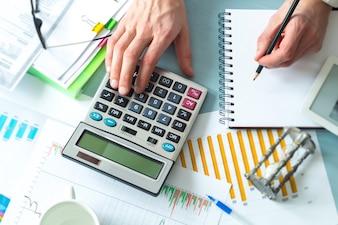Ein Geschäftsmann, ein Buchhalter, schreibt einen Bericht, indem er einen Taschenrechner verwendet, während er an einem Arbeitsplatz sitzt