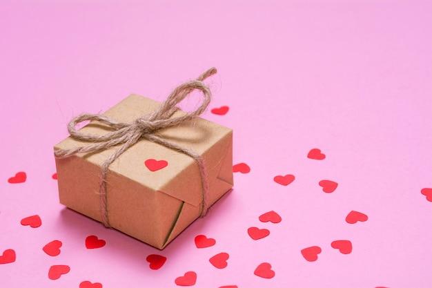 Ein geschenk, das in kraftpapier auf einem rosa hintergrund eingewickelt wird. rote papierherzen auf einer geschenkbox. Premium Fotos