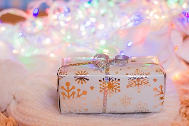 Ein geschenk eingewickelt in einer festlichen verpackung, die mit einem silbernen band auf einem gestrickten weißen produkt auf einem hintergrund des bokeh der verschiedenfarbigen lichter gebunden wird. weihnachtsvorbereitungen konzept