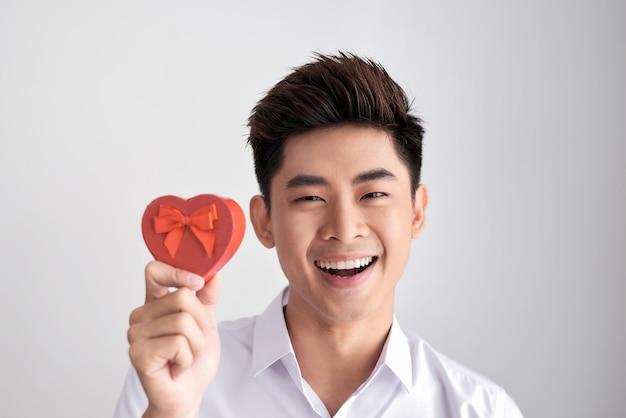 Ein geschenk für den geliebten. junger schöner lächelnder eleganter mann in einem weißen hemd, das eine schachtel mit einem geschenk hält und es der kamera zeigt. valentinstag.