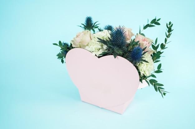 Ein geschenk für liebhaber am valentinstag. rosa herz. netter rosa herzförmiger korb für einen blumenstrauß