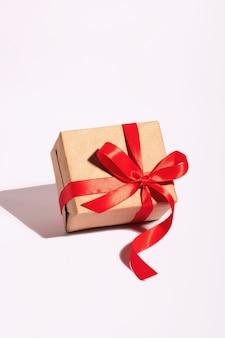 Ein geschenk in einem kraftpapier mit rotem band auf einem weißen hintergrund