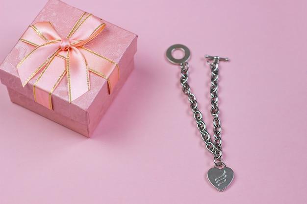 Ein geschenk in einem schönen kasten und in einer halskette mit einem herzen auf einem rosa hintergrund