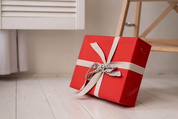 Ein geschenk in einer schachtel, die in festliches papier eingewickelt und mit einem satinband mit einer schleife gebunden ist. kopieren sie auf lila hintergrund speicherplatz.