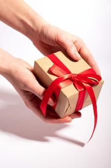 Ein geschenk mit einem roten band in den händen der frau auf einem weißen hintergrund