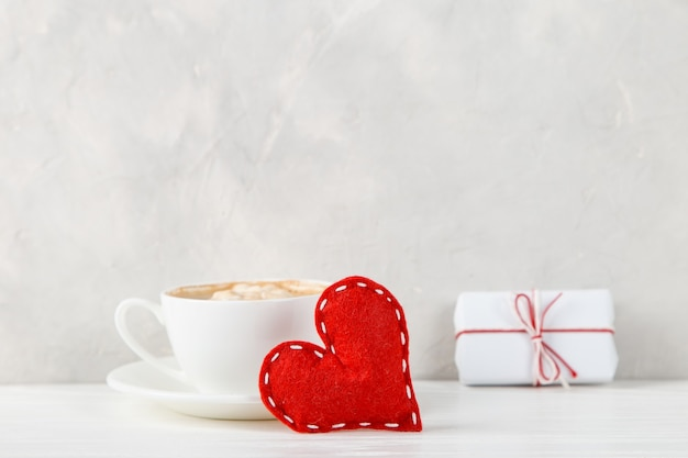 Ein geschenk, rotes herz, morgenkaffee gegen die einer hellen wand, konzept, eine postkarte für valentinstag.