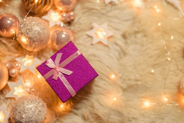 Ein geschenk unter goldenen und rosa weihnachtsspielzeugen und girlandenlichtern. flache lage, draufsicht, kopierraum.