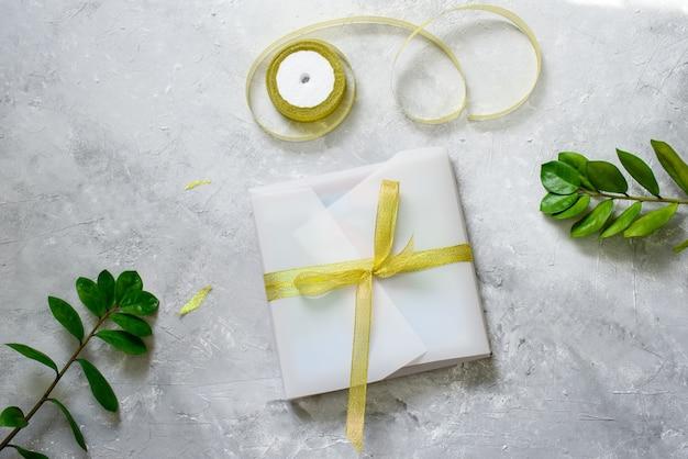 Ein geschenk verpacken, in schönes weißes papier, ein goldenes band. zweige grüner pflanzen, scheren. handgemachte verpackung.