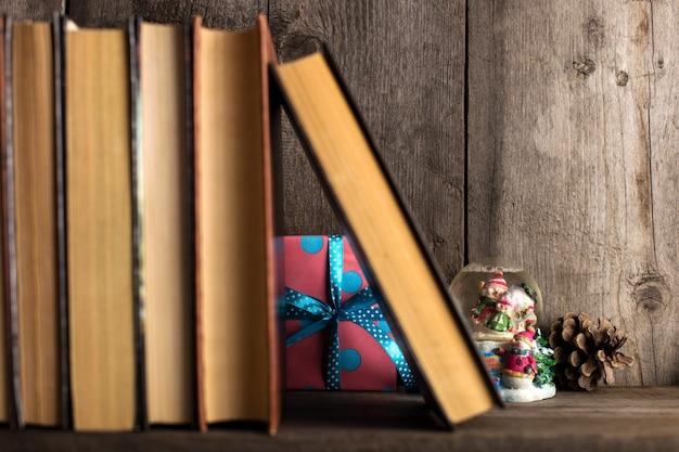 Ein geschenk versteckt auf einem holzregal hinter den büchern.