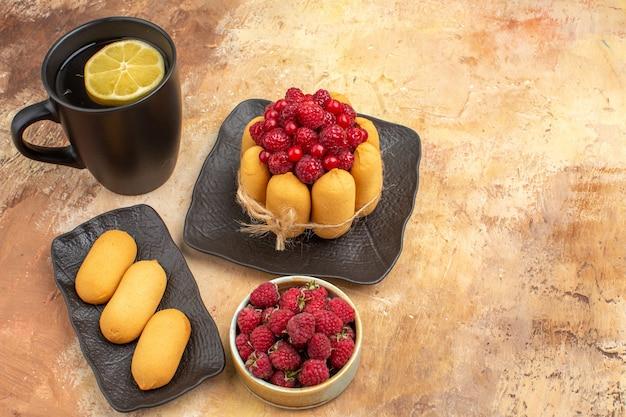 Ein geschenkkuchen und tee in einer schwarzen tasse mit zitrone und keksen auf gemischtem farbtisch
