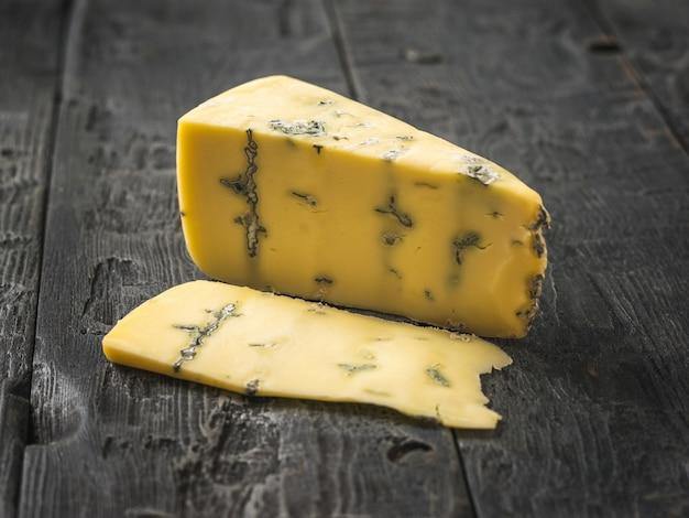 Ein geschnittenes stück frischkäse mit blauschimmel auf einem holztisch. käsespezialität. eine nützliche form