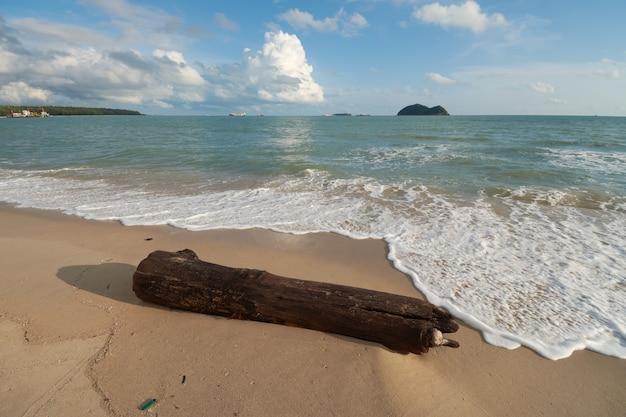 Ein gestrandetes holz mit inselhintergrund bei samila beach, songkhla, thailand.