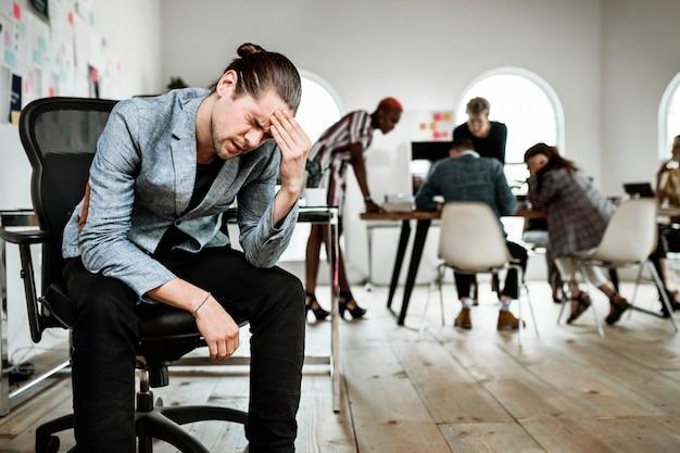 Ein gestresster geschäftsmann, der während eines meetings eine pause macht