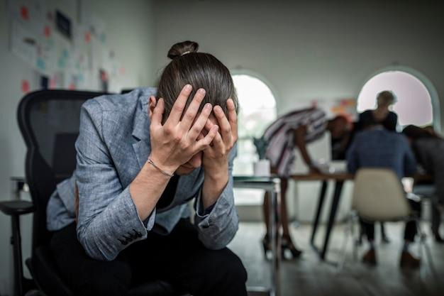 Ein gestresster geschäftsmann sitzt auf einem stuhl in einem büro