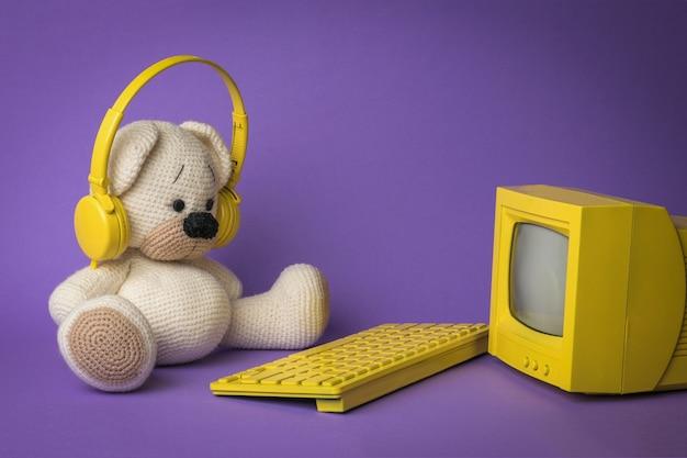 Ein gestrickter bär mit gelber tastatur vor einem gelben monitor auf violettem hintergrund.