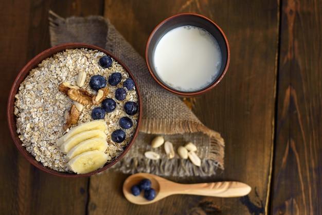 Ein gesundes frühstück auf dunklem holz: haferflocken, milch, nüsse und blaubeeren. draufsicht