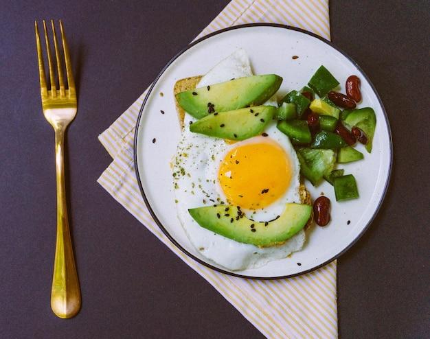 Ein gesundes frühstück aus toast mit avocado, vollkornbrot und spiegelei und burritosalat auf weißem teller. draufsicht
