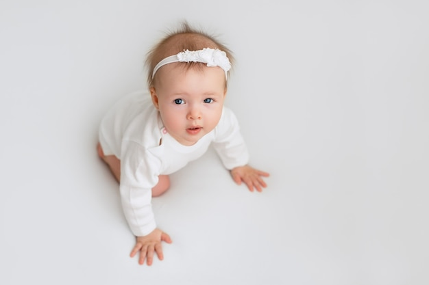 Ein gesundes kind auf einem weißen hintergrund schaut auf.