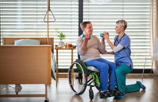Ein gesundheitspersonal und ein älterer patient im krankenhaus, physiotherapiekonzept.