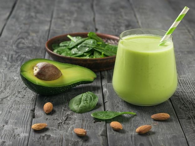 Ein getränk aus avocado, spinat und mandelmilch auf einem dunklen holztisch. fitnessprodukt. diätetische sporternährung.