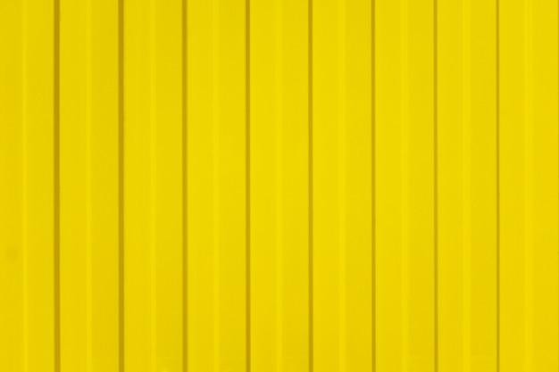 Ein gewölbter zaun der gelben blechtafeln mit schraube. textur der metallzaun