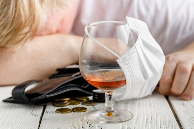 Ein glas alkohol mit einer medizinischen gesichtsmaske abdecken. konzept der abgesagten gesellschaftlichen ereignisse während der quarantäne von pandemien und koronaviren