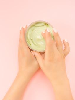 Ein glas anti-aging-creme wird in den händen einer frau mit schöner maniküre gehalten. naturkosmetik aus biologischem anbau. hautpflegeprodukt. die hände der frau, die schönheitscreme, lotion halten. rosa hintergrund