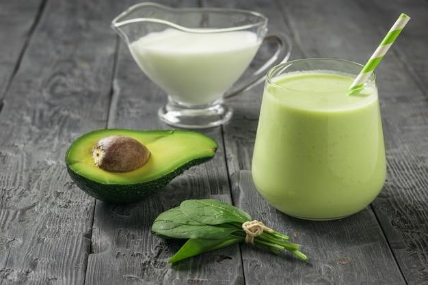 Ein glas avocado- und spinat-smoothies mit mandelmilch auf einem holztisch. fitnessprodukt. diätetische sporternährung.