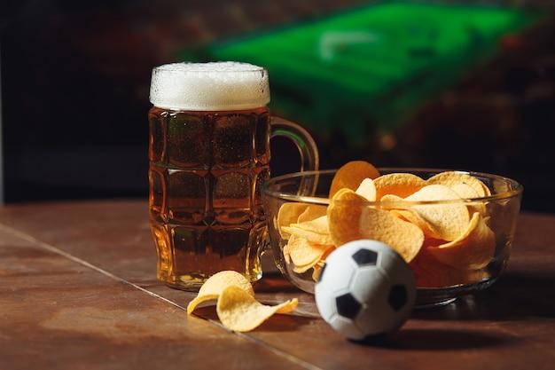 Ein glas bier auf einem holztisch mit kartoffelchips. fußball auf einem hintergrund