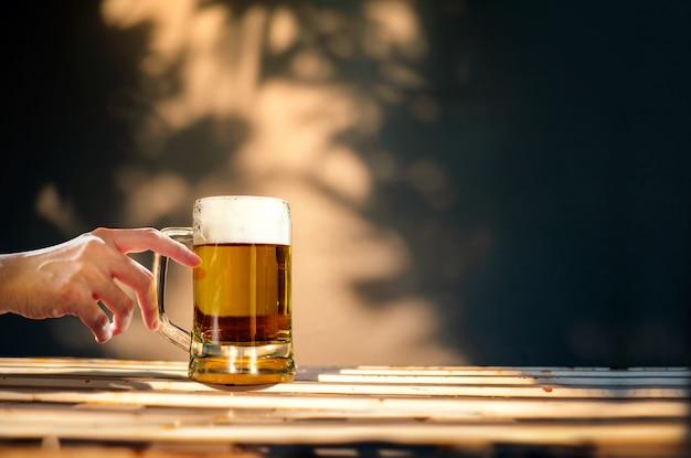 Ein glas bier auf tabelle in sommer sunny day. leute, die gebräu trinken