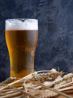 Ein glas bier gegen eine dunkle wand