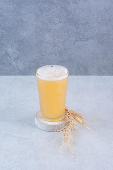 Ein glas bier mit weizen auf weißer oberfläche