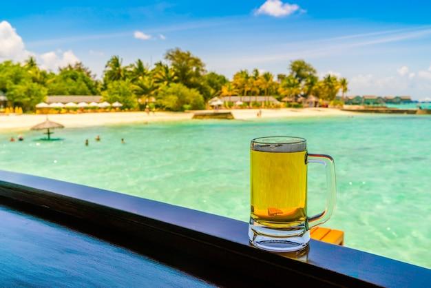 Ein glas bier mit wunderschönen tropischen malediven insel.