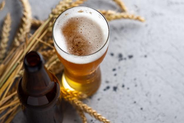 Ein glas bier und eine bierflasche auf der grauen steintischplatteansicht