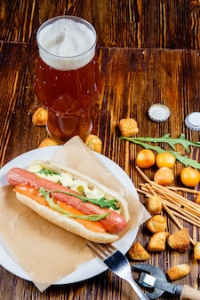 Ein glas bier und snacks auf einem holztisch.