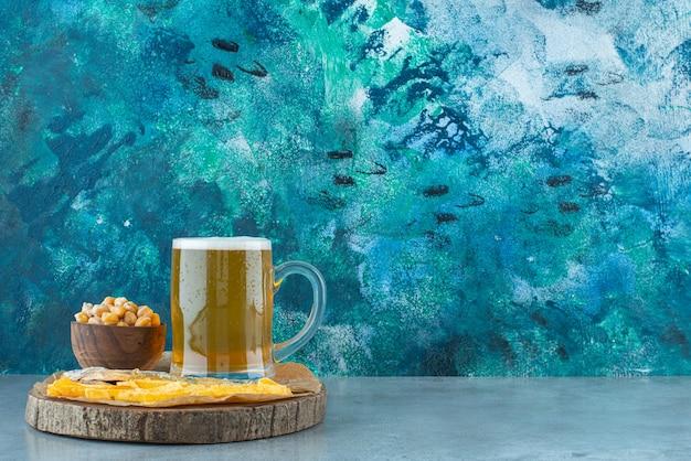 Ein glas bier und vorspeisen an bord auf blau.