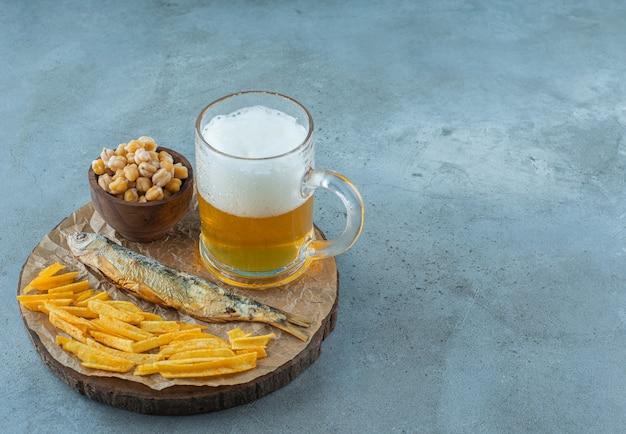 Ein glas bier und vorspeisen an bord, auf dem blauen tisch.