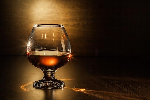 Ein glas brandy auf dem holztisch.
