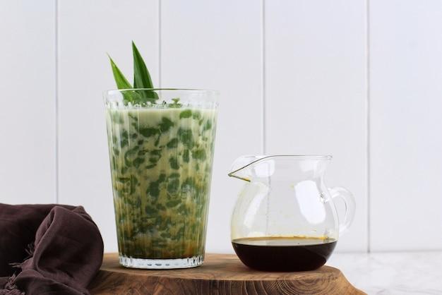 Ein glas cendol oder dawet ist indonesiens traditionelles eisdessert aus reismehl, palmzucker, kokosmilch und pandablatt, das in glas auf weißem tisch serviert wird. beliebt beim fasten im ramadan.