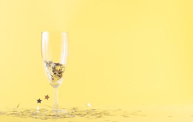 Ein glas champagner gefüllt mit grauen sternen auf gelbem grund. um das gehäuse herum schweben graue sterne in der luft. party- und feierkonzept mit großem kopienraum