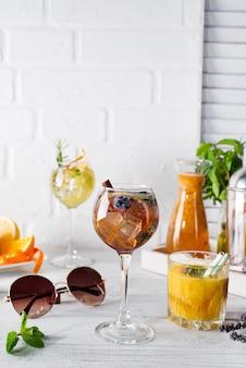 Ein Glas Cocktail mit Zimt, Beeren und braunem Zucker und ein Glas mit einem Orangenschwanz