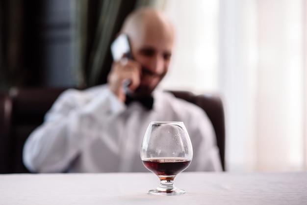 Ein glas cognac auf einem hintergrund von männern