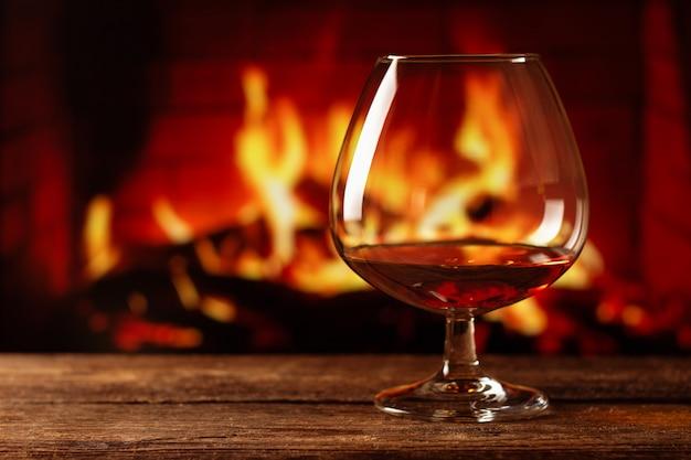 Ein glas cognac mit verschwommenem lagerfeuer
