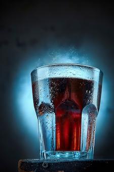 Ein glas cola steht vor einer betonwand