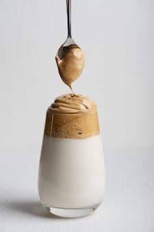Ein glas dalgona-kaffee aus instantkaffee und kalter milch auf weißem holztisch