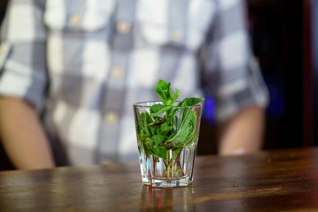 Ein glas, das mit niederlassungen einer wohlriechenden minze gefüllt wird, stehen auf holztisch auf eines mannes in einem karierten hemd.
