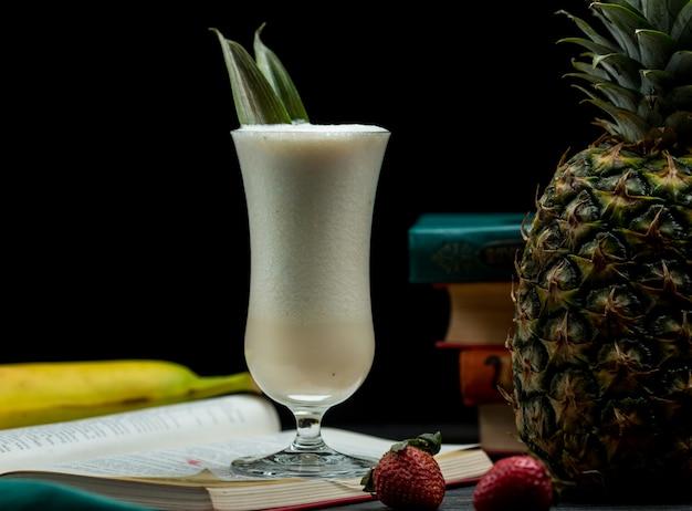 Ein glas des vollen mischcocktails der tropischen früchte, das auf einem buch steht, verlässt